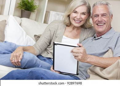 Happy senior man and woman couple sitting together at home smiling and happy using a tablet computer