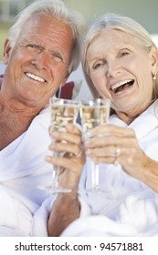 Happy senior man and woman couple sitting together outside in sunshine wearing white bathrobes celebrating drinking white wine Champagne