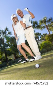 Happy senior man and woman couple together playing golf and putting on a green, celebrating the ball going in the hole, a successful shot