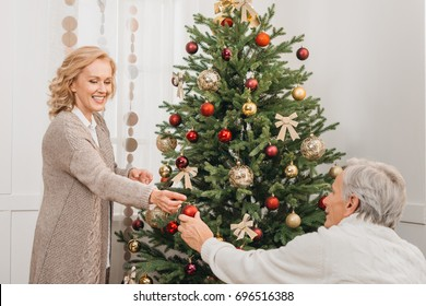 happy senior man and woman decorating christmas tree together