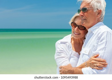 Happy senior man and woman retired couple embracing wearing sunglasses on a deserted tropical beach with turquoise sea and clear blue sky