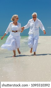 Happy senior man and woman retired couple wearing sunglasses holding hands and running on a deserted tropical beach with clear blue sky