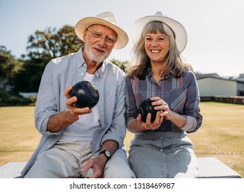 Happy senior man and woman sitting together in a park holding boules. Smiling elderly couple wearing hats enjoying their time sitting in a boules park.