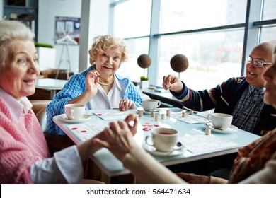 Happy senior man and women playing lotto and having tea