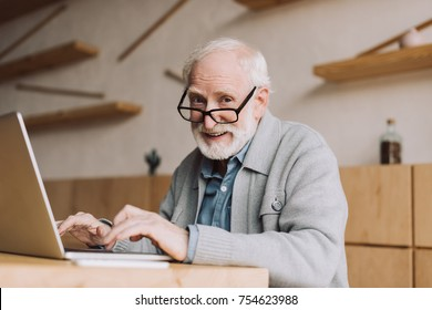 happy senior man working with laptop and looking at camera