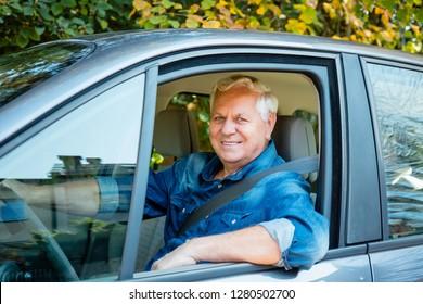 Happy senior man working as uber taxi driver, smiling at camera.