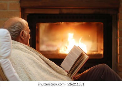Happy senior man, wrapped in warm knitted plaid, relaxing at home in the evening, sitting in rocking chair by fireplace and reading a book - successful retirement concept