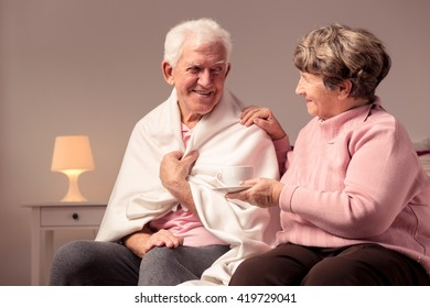 Happy senior married couple, positive senior woman holding a white cup