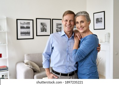 Happy senior mature 60s family couple hugging, looking at camera, standing in living room in modern apartment. Smiling satisfied middle aged husband and wife embracing posing for portrait at new home.