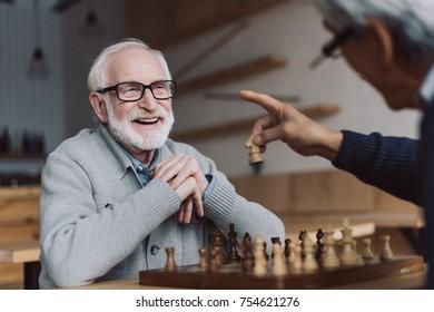 happy senior men playing chess in bar
