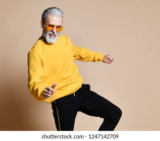 Happy senior millionaire man dancing in yellow sunglasses stylish fashionable men senior on beige background