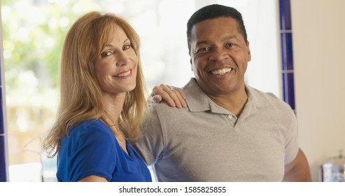 Happy Senior mixed race couple homeowners looking at camera. Older Caucasian and African American husband and wife standing in their kitchen smiling