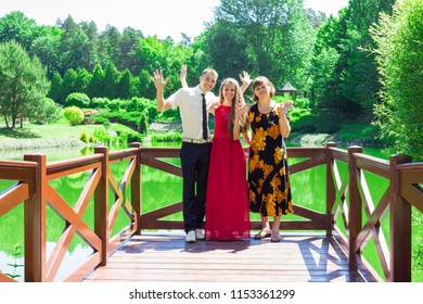 Happy senior mother with adult daughter and son walk in beautiful summer garden. Big happy stylish family
