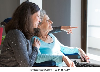 Happy senior mother and adult daughter enjoying dramatic view out of window. Elderly lady resting in armchair, while young woman pointing out of window. Scene from window concept