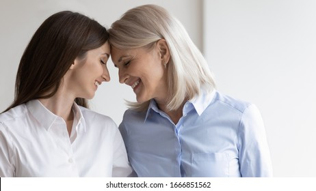 Happy senior mother and adult daughter touch foreheads hug cuddle show love and care, smiling mature mom and grown-up girl enjoy tender close moment at home together, family bonding concept