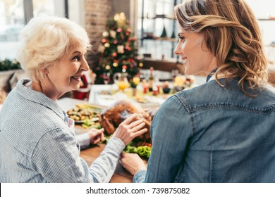 happy senior mother and daughter celebrating christmas together