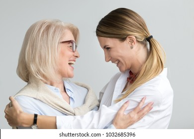 Happy senior mother embracing adult daughter laughing together, smiling excited aged older lady hugging young woman, sincere family of different age generations bonding talking joking having fun