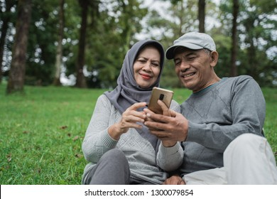 happy senior muslim couple using smartphone together in the park. old people with modern technology
