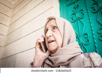 Happy senior Muslim woman talking on phone