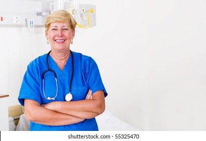 Happy senior nurse standing with hands folded in hospital ward
