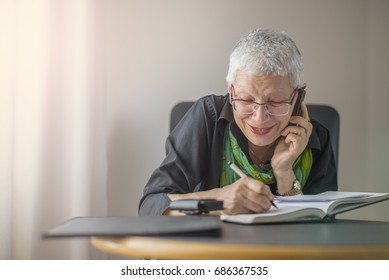 Happy senior old business woman writing down orders, talking on