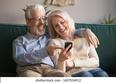 Happy senior old couple holding smartphone looking at cellphone screen laughing relaxing sit on sofa together, smiling elder mature grandparents family embracing having fun with mobile phone at home