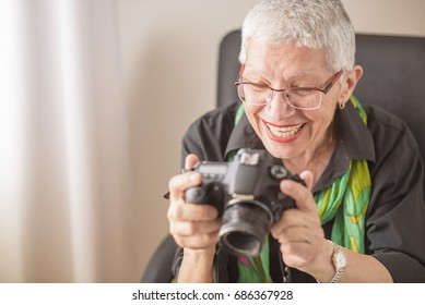 Happy senior old woman reviewing photos on the back of her DSLR camera LCD screen