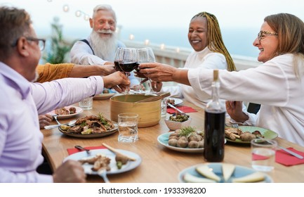 Happy senior people cheering with red wine at dinner outdoor on patio - Concept of friendship