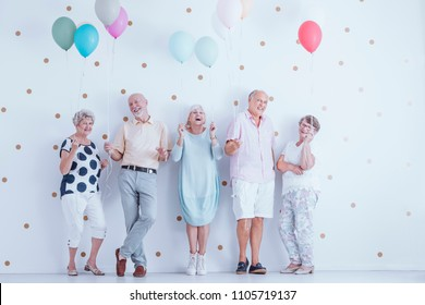 Happy senior people with colorful balloons celebrating friend's birthday