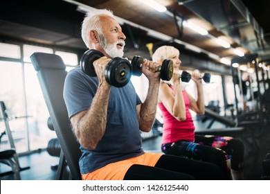 Des personnes âgées heureuses faisant des exercices en salle de gym pour rester en forme
