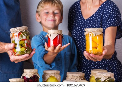 Happy senior people, grandmother, grandfather and young boy, grandson holding in hands jars with homemade preserved and fermented food, pickled and marinated. Harvest preservation, family time