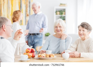 Happy senior people spending afternoon together at nursing home sitting at table and drinking tea