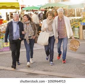 Happy senior people walking at the green market