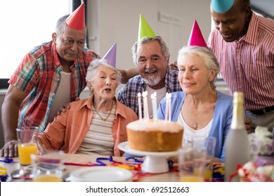 Happy senior people wearing party hats celebrating birthday at nursing home