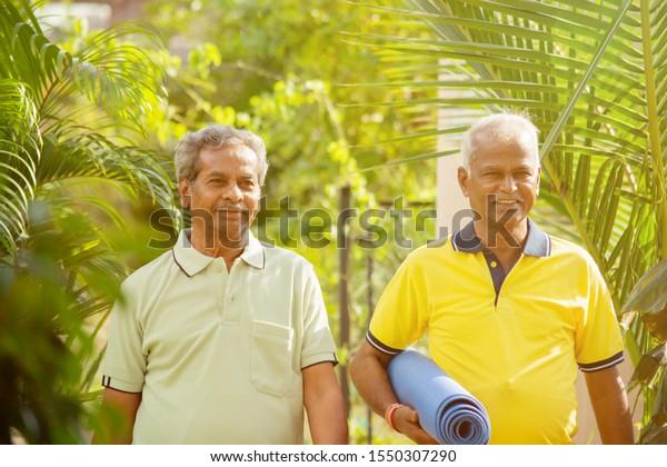 Happy Senior people with yoga mat in park - Healthy elderly men with fitness mat outdoor - older joyful friends walking in garden during morning.