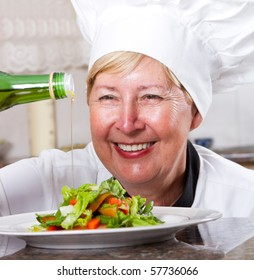happy senior professional chef pouring olive oil on salad