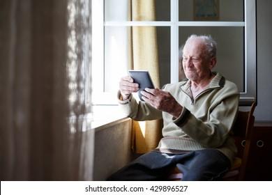 Happy Senior entspannen zu Hause und mit Tablet.