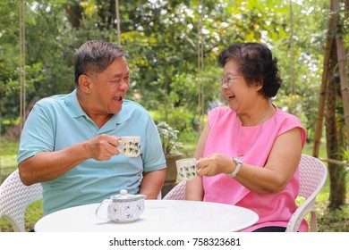 Happy senior retired Asian couple laughing, smiling and drinking tea in outdoor garden.