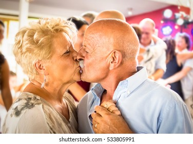 Happy senior retired couple having fun on dancing at restaurant wedding celebration party - Love concept of joyful elderly and retirement lifestyle with man lovely kissing wife - High iso color image