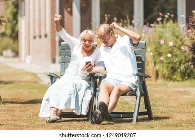Happy senior (retired) couple in love watching  smartphone with raised hands and screaming - two old people sitting in the garden