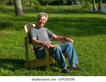 Happy senior siting in a wooden Muskoka / Adirondack chair near a river