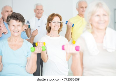 Happy senior sportspeople exercising with dumbbells in a fitness center