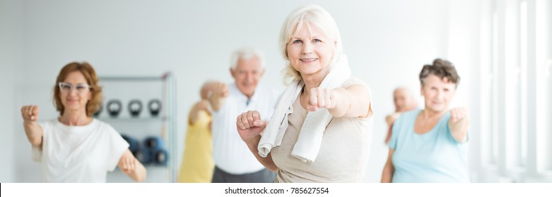 Happy senior sportswoman with a towel around her neck exercising with friends in a fitness studio
