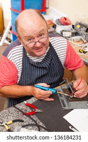 happy senior technician working with soldering iron in workshop