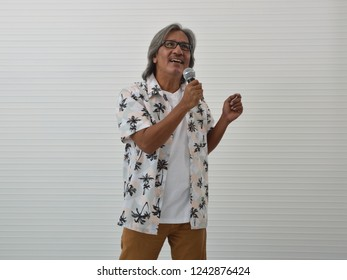 Happy senior traveler asian man wearing glasses, summer shirt and brown shorts singing with microphone over white wall background, Summer holiday concept