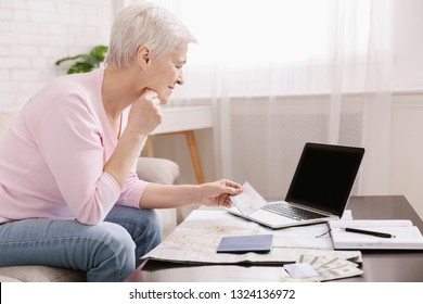 Happy senior traveller looking at blank laptop screen, anticipating future trip, copy space