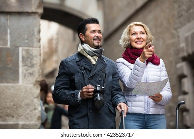 Happy senior travellers couple with camera checking city map and sightseeing
