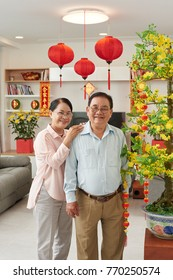 Happy senior Vietnamese couple at home decorated for tet celebration; couplets with best wishes for the upcoming year in the background