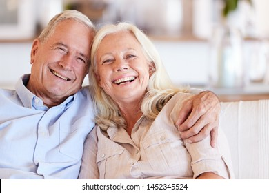 Happy senior white couple sitting at home embracing and smiling to camera, front view, close up