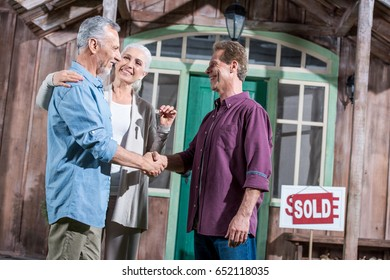 happy senior wife holding keys of new house while her husband shaking hands with saleman